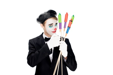clown in suit and black beret holding firecrackers isolated on white