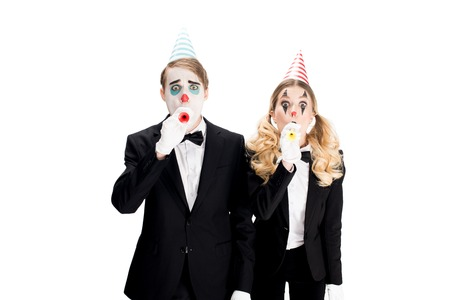 couple of clowns in suits blowing in birthday blowers isolated on white