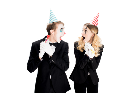 couple of clowns in suits looking at each other and holding birthday blowers isolated on white Standard-Bild