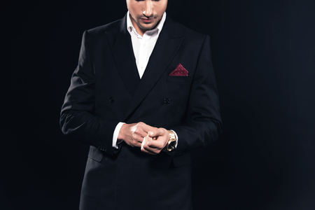 cropped view of man in suit putting on watch isolated on black