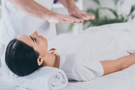 young woman lying on massage table and receiving reiki treatment Imagens