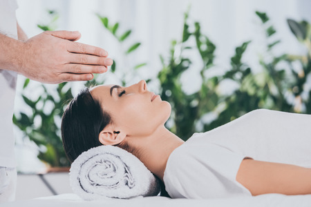 cropped shot of young woman receiving reiki treatment above head