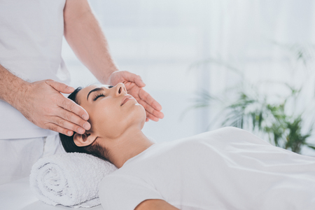 cropped shot of calm young woman with closed eyes receiving reiki healing treatment