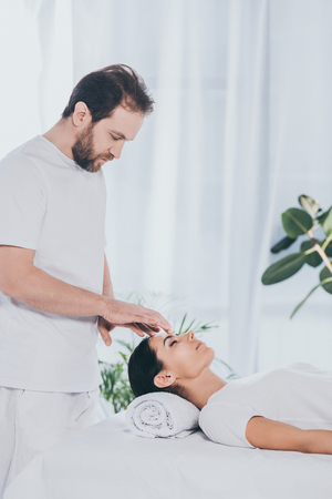 side view of bearded healer doing reiki treatment session to young woman with closed eyes