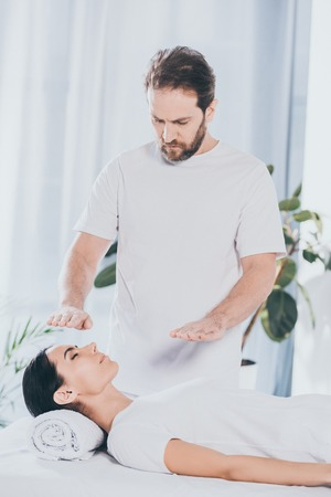 bearded healer doing reiki treatment session to young woman with closed eyes Stock Photo