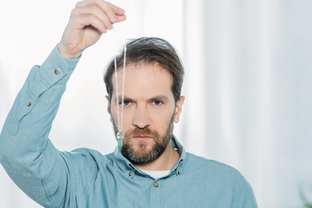 serious bearded male hypnotist holding dowsing and looking at camera