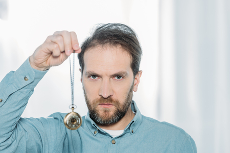 serious bearded hypnotist holding dowsing and looking at camera