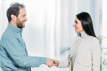 side view of psychotherapist and patient shaking hands and smiling each other Stock Photo