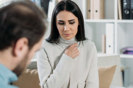 selective focus of unhappy young patient looking down while talking with psychotherapist in office Stock Photo - 117780071