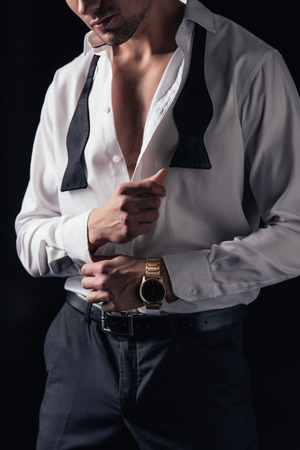 cropped view of man buttoning up white shirt isolated on black