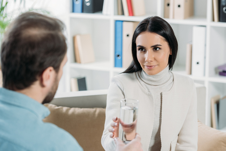 young woman holding glass of water and looking at psychotherapist in office