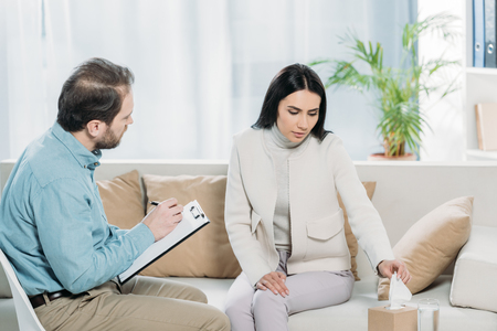 upset young woman holding paper tissue during therapy session with psychiatrist