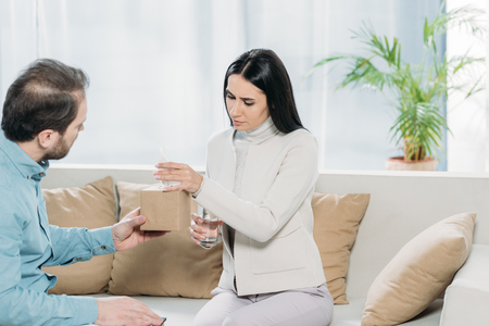 psychotherapist with clipboard giving paper tissues to upset young patient with glass of water Stock Photo