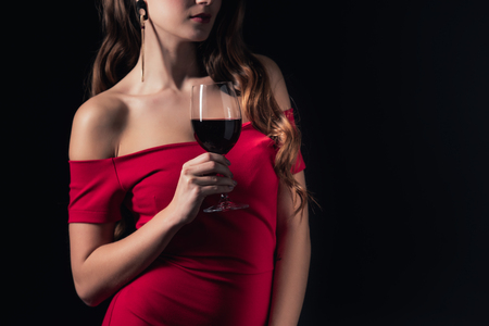 partial view of woman in red dress holding glass of red wine isolated on black