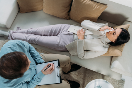 overhead view of psychotherapist writing on clipboard and young patient crying on couch Stock Photo - 117780234
