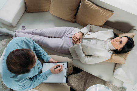 overhead view of psychotherapist writing on clipboard and upset young patient lying on couch Stock Photo - 117780318
