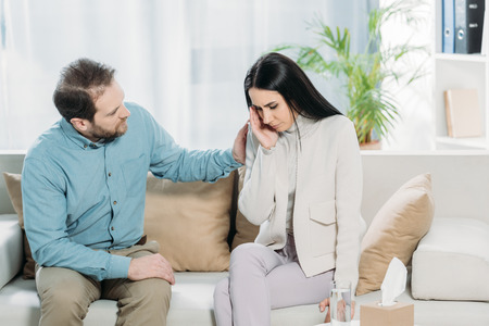 bearded psychotherapist supporting young upset woman crying on couch