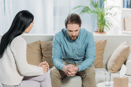 young psychotherapist talking with upset bearded man sitting on couch Stock Photo