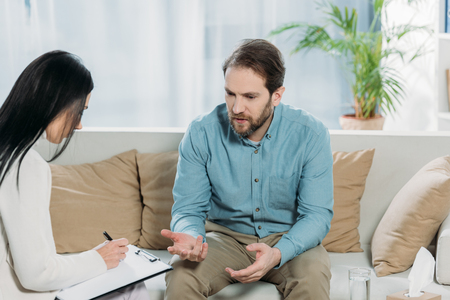 psychotherapist writing on clipboard and unhappy bearded man sitting on couch and talking