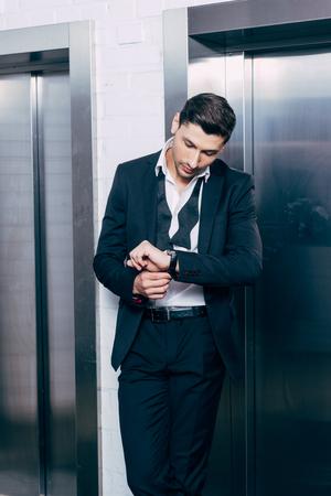 man in black suit putting on watch near elevators