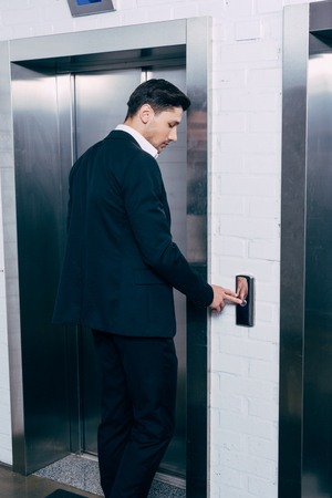 man in black suit pressing elevator button 스톡 콘텐츠