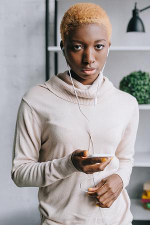 selective focus of african american woman listening music in earphones