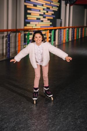Little roller skater skating with sincere smile 스톡 콘텐츠