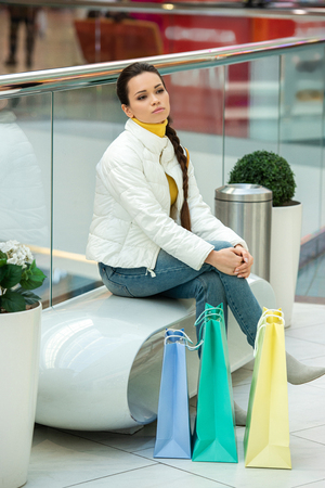 thoughtful girl with shopping bags sitting on bench in mall Stockfoto