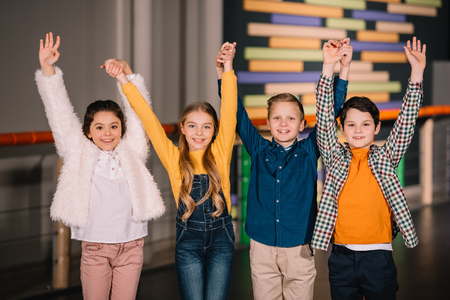 Children raising hands up and expressing happy emotions Фото со стока