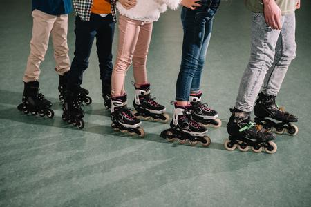 Cropped shot of several kids skating on rink