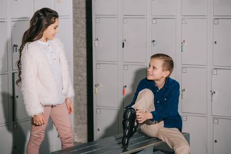 Indoor shot of kids putting on skates in locker room 版權商用圖片