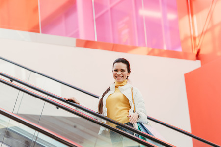 attractive girl with shopping bags smiling and looking at camera on escalator Banco de Imagens