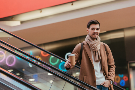 handsome man holding disposable cup, smiling and looking at camera on escalator
