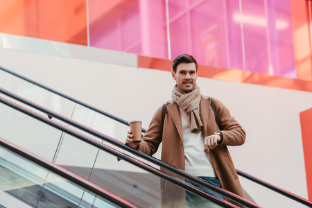 handsome man in warm clothing holding disposable cup, smiling and looking at camera on escalator Banco de Imagens