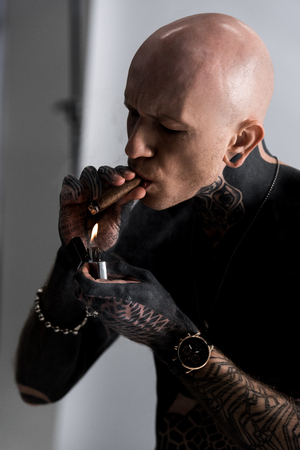 bald shirtless tattooed man holding lighter and smoking cigar on grey