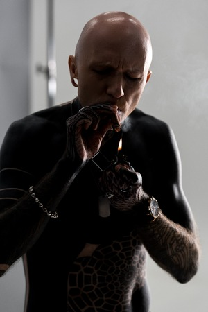 bare-chested man with tattoos lighting cigar with lighter on grey