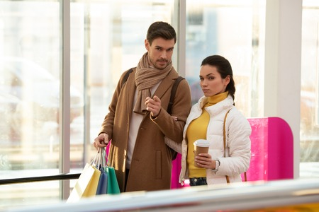 handsome man with shopping bags pointing with finger at camera and attractive girl holding disposable cup