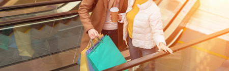 cropped view of couple holding shopping bags and disposable cup on escalator