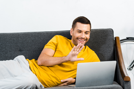 handsome man lying on sofa and waving to say hello while having video call
