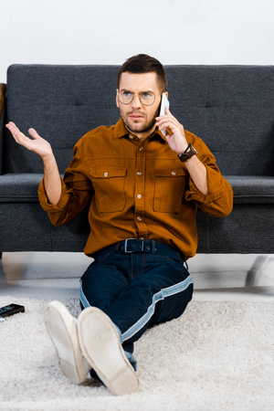dissatisfied man sitting on carpet and talking on smartphone