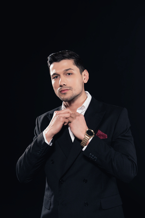 handsome man in suit looking at camera and buttoning up shirt isolated on black