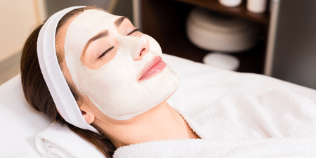 woman lying in white bathrobe with applied facial mask and smiling at beauty salon