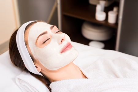 woman lying in white bathrobe with applied facial mask, smiling and closed eyes at beauty salon