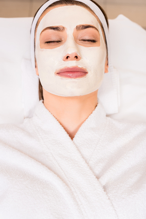 top view of woman lying in white bathrobe with applied face mask at beauty salon Stock fotó - 116556424