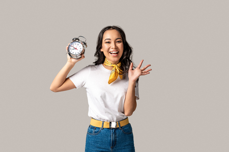 Happy asian woman in white t-shirt and blue jeans holding alarm clock and waving hand isolated on grey
