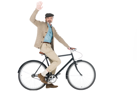 cheerful pensioner riding bicycle and waving hand isolated on white