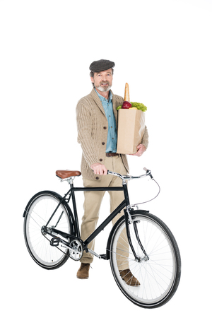 cheerful pensioner smiling whole hoding paper bag with groceries and bicycle isolated on white