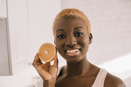 close up of cheerful african american woman holding half of orange Reklamní fotografie