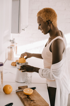 side view of attractive african american woman squeezing orange Stockfoto