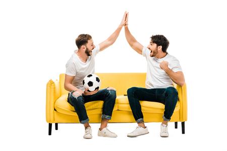 Feliz joven sentado en el sofá con un balón de fútbol y dando cinco aislado en blanco